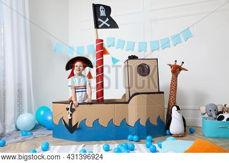 Cute Little Boy Playing With Pirate Cardboard Ship And Toys At Home. Child's Room Interior