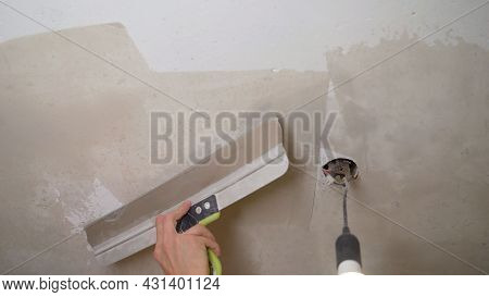 The Plasterer Levels The Wall Before Gluing The Wallpaper. The Process Of Leveling The Wall With Put