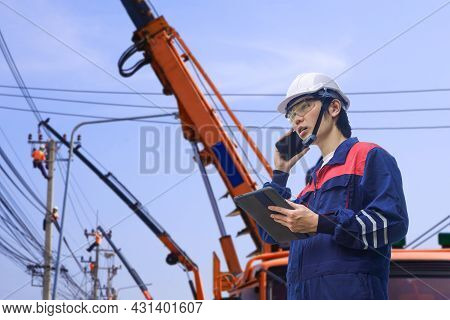 Asian Engineer Holding Tablet And Using Smartphone While Controlling His Electric Teamwork Are Worki
