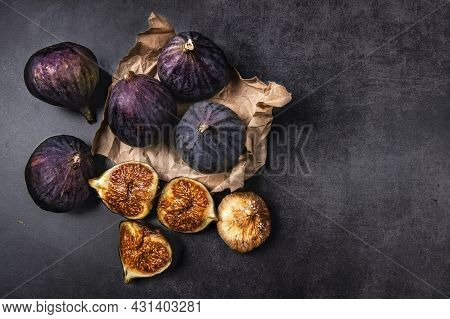 Fresh And Dried Figs On A Dark Background. Several Ripe Figs, One Cut And Dried Figs Lie On A Dark C