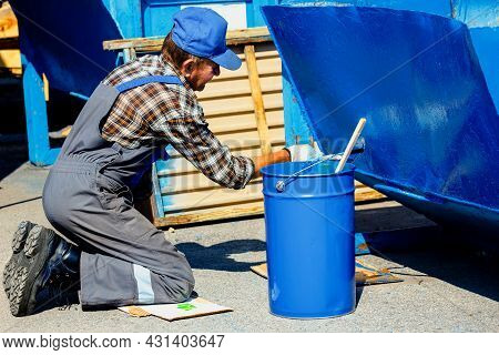 An Old Man In A Work Jumpsuit Paints A Garbage Can Or Container On The Street With A Paint Brush. Pa
