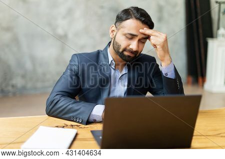 Upset Indian Businessman In Formal Suit Has Strong Headache, Sitting In Front Of Laptop And Holding