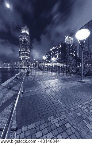 Seaside Promenade Of Victoria Harbor In Hong Kong City At Night
