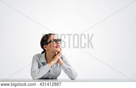 Charming Young Woman Sits At Desk And Dreamy Looking Upward. Portrait Of Beautiful Girl In Glasses W
