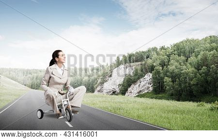 Beautiful Caucasian Woman Riding Kids Bicycle On Asphalt Road. Young Employee In White Business Suit