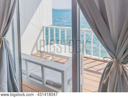 The View From The Interior Of A Room With White Curtains Looking Through The Window Overlooking A Ba