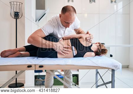 Charming Female Lying On Massage Table While Doctor Osteopath Examining Her Body In Medical Center