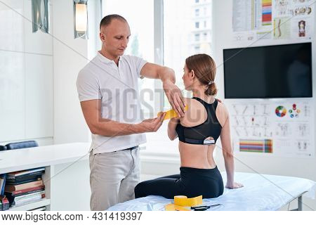 Young Woman Sitting On Massage While Doctor Osteopath Applying Yellow Tape In Medical Office