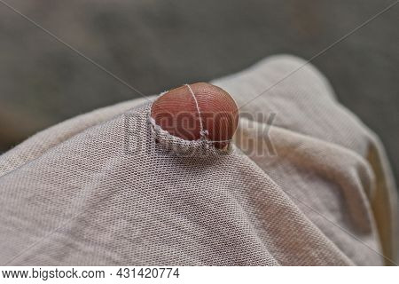 One Finger In A Hole In Torn Gray Woolen Fabric Of Old Clothes