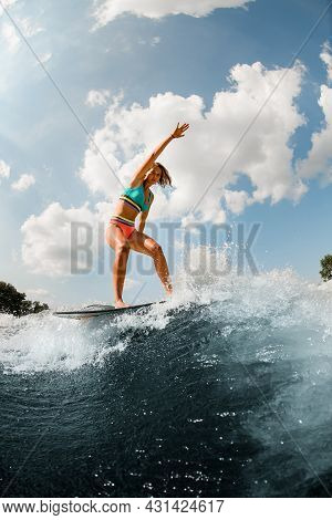 Active Woman In Colorful Swimsuit Energetically Balancing On Wave On Wakesurf Board.