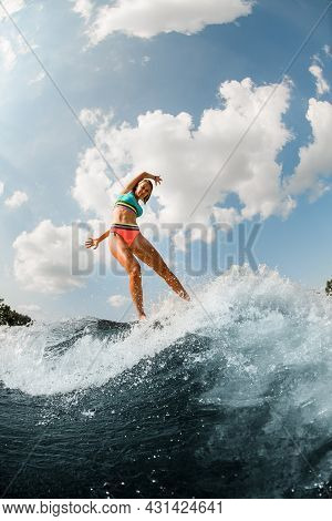 Young Athletic Woman In Colorful Swimsuit Energetically Balancing On Wave On Wakesurf Board.