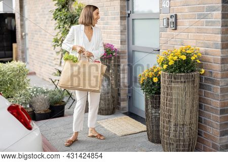 Young Business Woman Going Home With Groceries, Standing With Shopping Bag On The Porch Of Her House