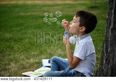 Adorable Elementary Aged School Boy Enjoying His Recreation Between Classes, Blowing Soap Bubbles, S