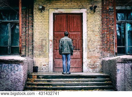Rear View Of A Man In Front Of The Old House Before The Closed Door