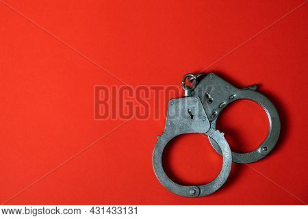 Handcuffs On The Red Paper Background Closeup