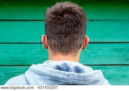 Young Man Rear View On The Wooden Wall Background Closeup