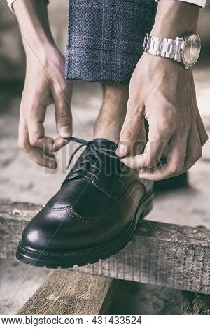Close-up Young Man Ties His Shoelaces On Stylish Black Shoes, Image Toned