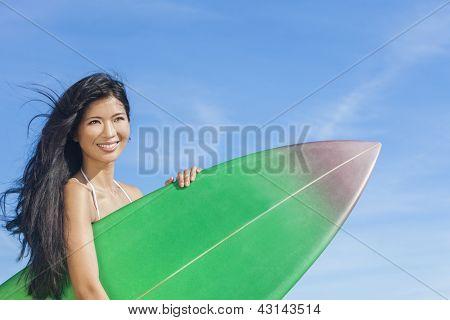 Beautiful young Asian Hawaiian woman surfer girl in bikini with surfboard standing on a beach with blue sky