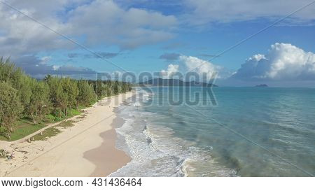 Colorful Aerial View Of Tropical Beach With Turquoise Blue Ocean Water And Waves Lapping On Hidden W