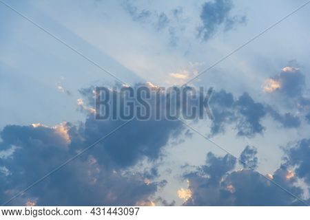 Evening Blue Sky With Clouds At Sunset. Clouds Are Illuminated By The Rays Of The Setting Sun.