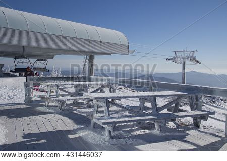 Tables On The Top Of A Snow-covered Mountain. The Background Of The Winter Space Of The Ski Lift And