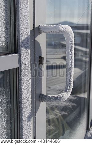 A Frozen Door Handle. The White Front Door Is Covered With Snow After A Blizzard.