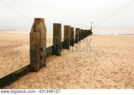 Wooden Breakwater Leading Across Stony Sand Beach To Sea On Dull Day