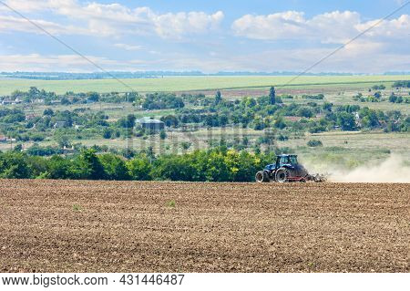 The Tractor In The Field Shallow Plow The Soil With Metal Discs After The Harvest.