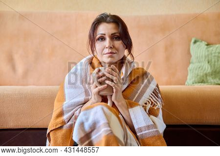 Middle-aged Woman Under Warm Woolen Blanket With Cup Of Hot Drink