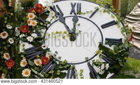 Large Wall Clock On The Field In Blooming Flowers, Showing The Time 11:55, 12:00. Time Management Co
