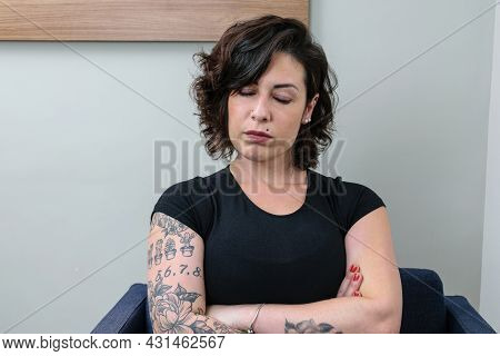 Brazilian Woman, Tattooed, With Arms Crossed And Eyes Closed. Upset And Angry.