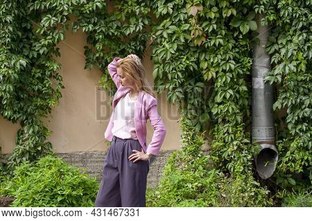 Young Elegant Beautiful Blonde Millennial With Long Hair In Pink Clothes Stands And Straightens Her