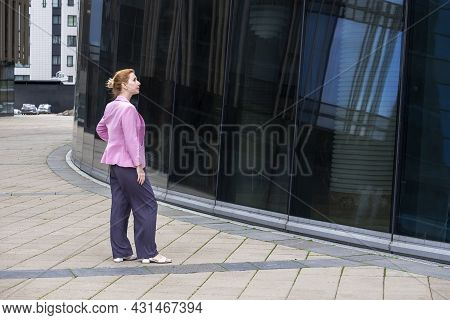 Young Blonde Woman With Tailored Hairstyle In Pink Jacket Stands In Front Of Modern Office Building