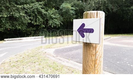 Wooden Arrow Purple Pointing The Direction Of Footpath For Hike Trail Escape City Path In Park