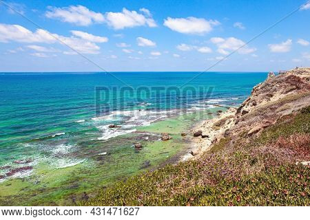 Sea surf with white foam of waves. Apollonia Park, Israel. Mediterranean coast. Picturesque ruins of the medieval citadel of Arsuf