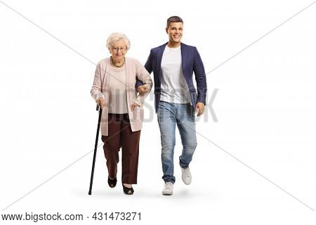 Full length portrait of a young man helping an elderly lady with a walking cane isolated on white background