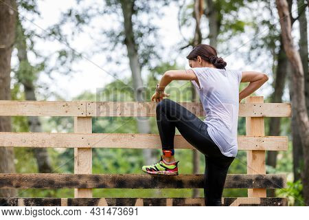 Young Sportswoman Climbing Timber Wall On Her Obstacle Race Course