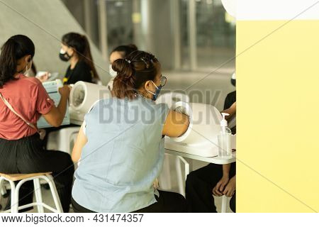 Woman In Protective Mask Arm Insert To Auto Measure Blood Pressure Machine And Heart Rate.