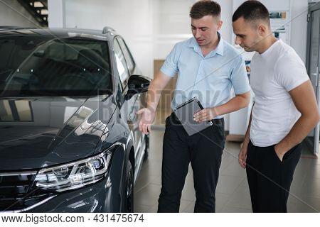 Salesperson Selling Cars At Car Dealership. Man Choosing Car In Car Showroom
