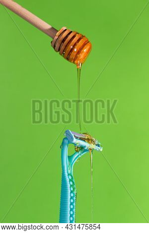 Sugar Paste For Hair Removal Against A Razor. Sugaring Paste Drips On A Razor On A Green Background.