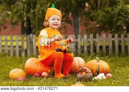 A Smiling Little Girl In A Halloween Costume Is Sitting On The Lawn Surrounded By Pumpkins And Holdi