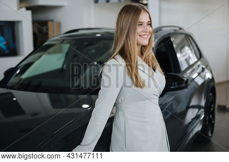 Portrait Of Gorgeous Woman In Showroom. Beautiful Salesperson Standing By Car. Blond Hair Female Aft