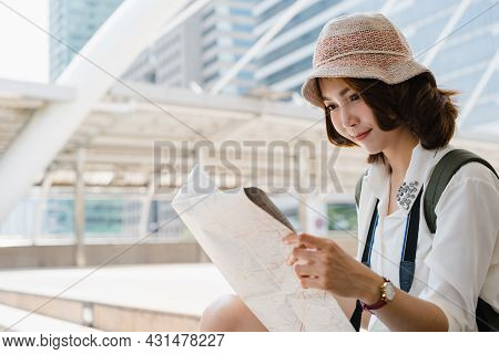 Happy Asian Woman Traveler Tourist Wanderer With Trendy Look Searching Direction On Location Map Whi