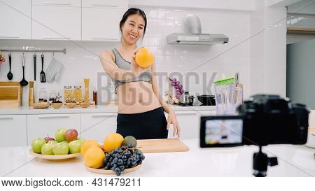 Blogger Sporty Asian Woman Using Camera Recording How To Make Orange Juice Video For Her Subscriber,