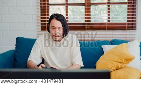 Asian Man Using Joystick Playing Video Games In Television In Living Room, Male Feeling Happy Using