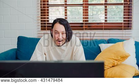 Asian Man Watching Television In Living Room At Home, Male Feeling Happy Lying On Sofa In Living Roo