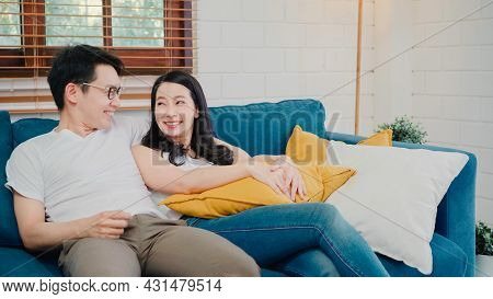Asian Couple Hug Together In Living Room At Home, Sweet Couple Enjoy Love Moment While Lying On The