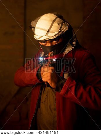 Terrorist Or Gangster With Face Cover Pointing Gun To Camera In Abandoned Place