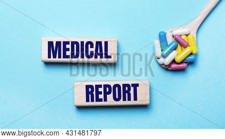 On A Light Blue Background, Bright Multi-colored Pills In A Spoon And Two Wooden Blocks With The Tex
