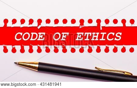 Pen And White Torn Paper Strip On A Bright Red Background With The Text Code Of Ethics